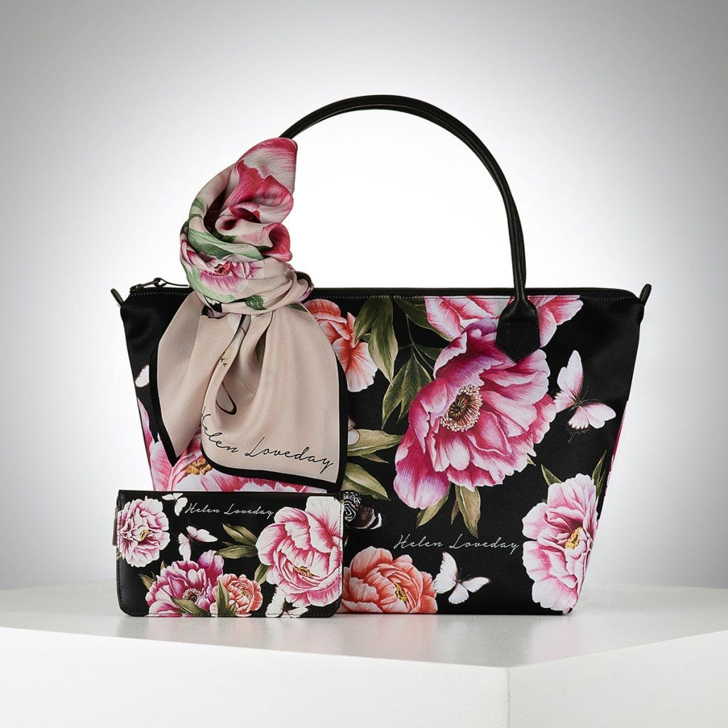 Black bag with pink flowers, grouped and presented creatively with gradient lighting. Showing creative product photography.