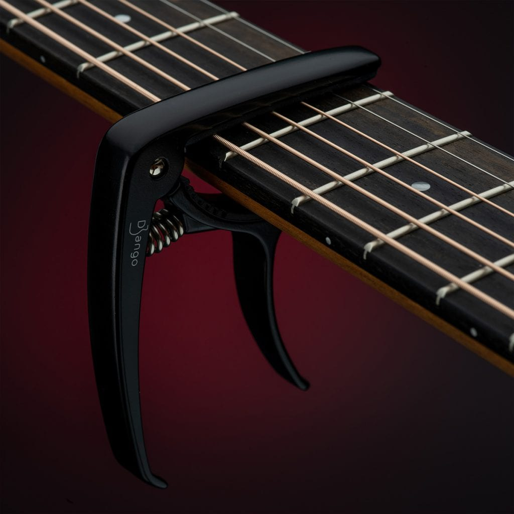Black Capo on a guitar neck with red gradient background, a creative shot we did for product photography.