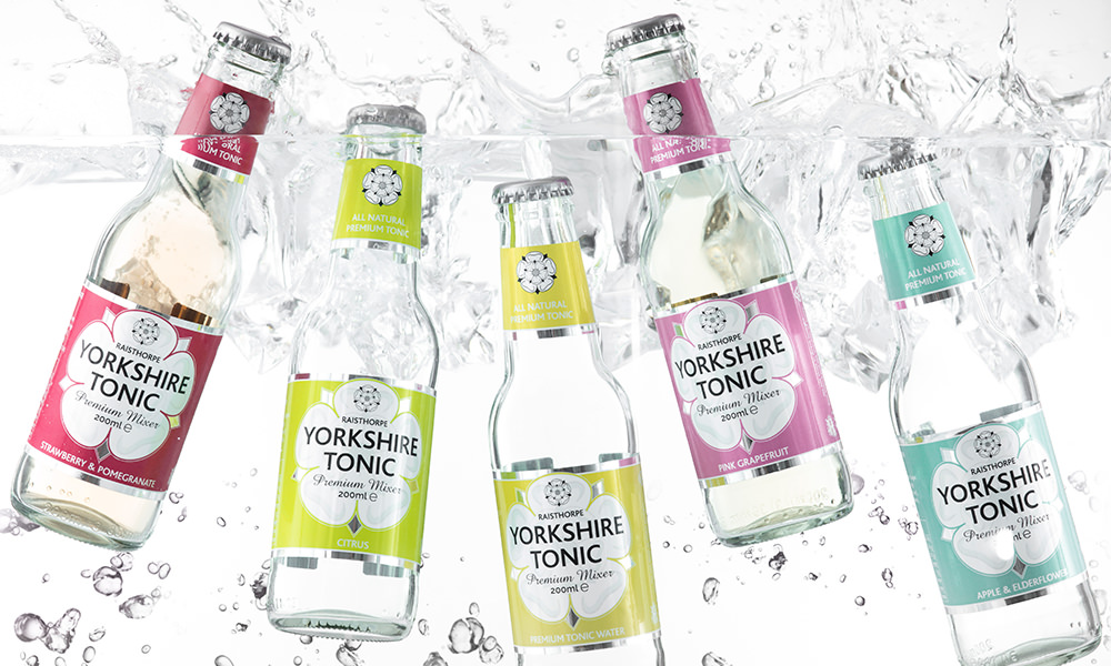 Creative product photography of Yorkshire tonic bottles splashing into water.