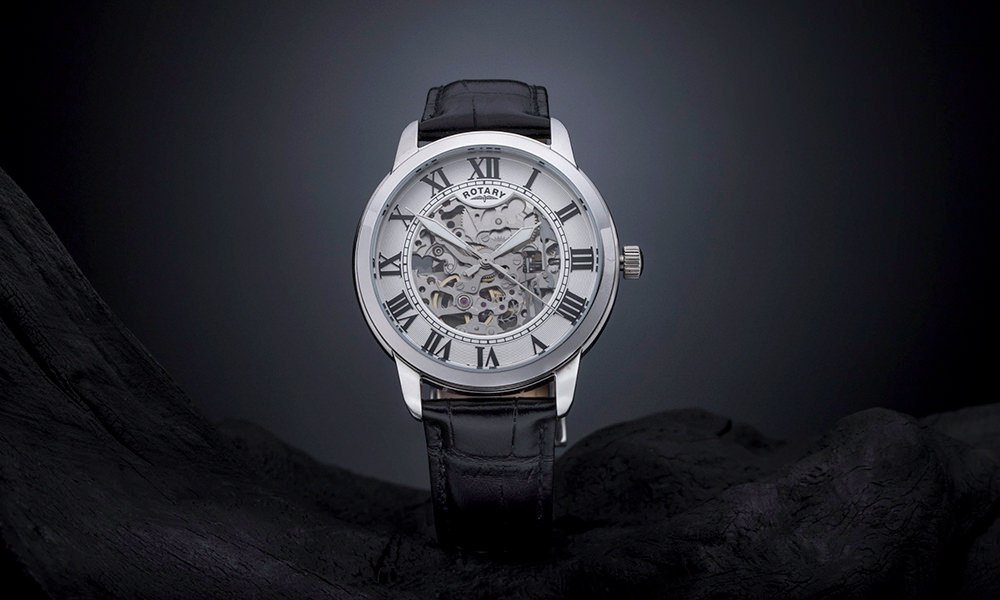 Creative product photography showing a rotary watch on stone and a grey gradient background.