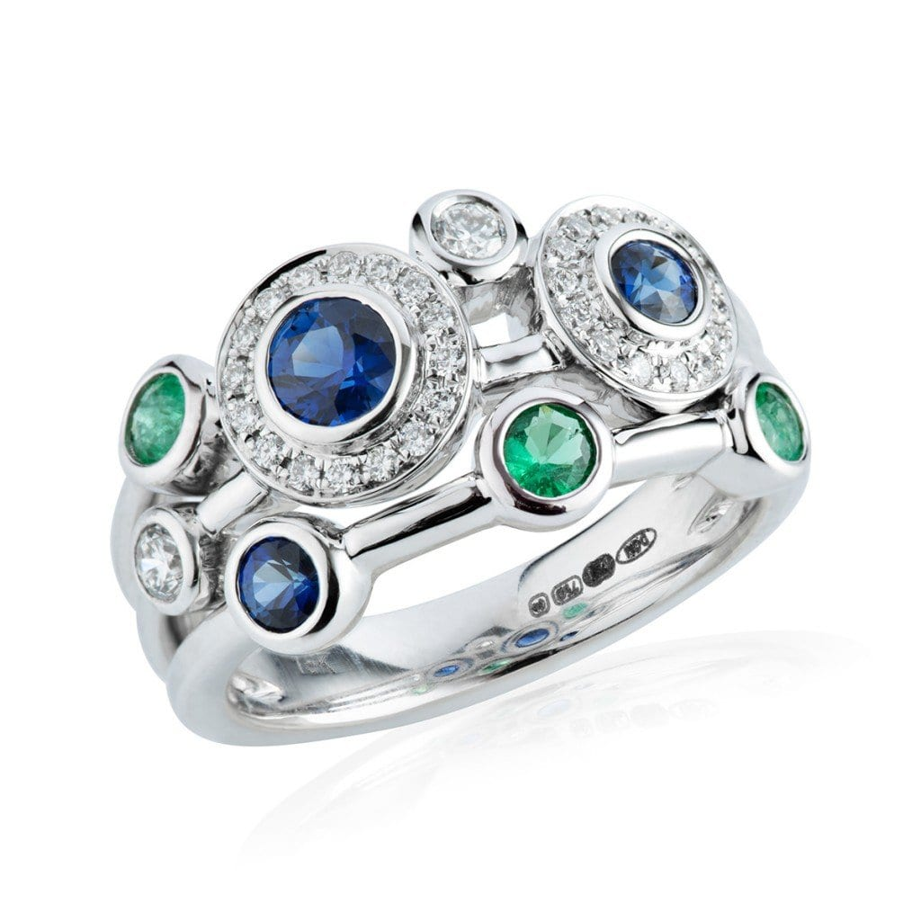 Silver ring with multiple blue and green stones, with clear gems, for jewellery product photography.