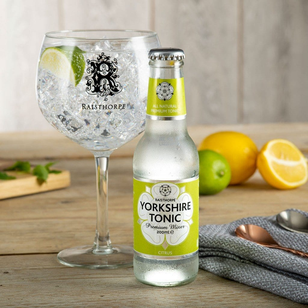 Condensed bottle of tonic with gin glass and fruit, a lifestyle product photograph.
