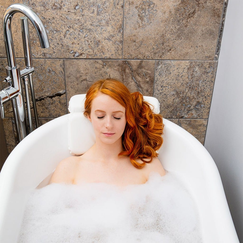 Model photography with a redhead model, showcasing a bath pillow product.