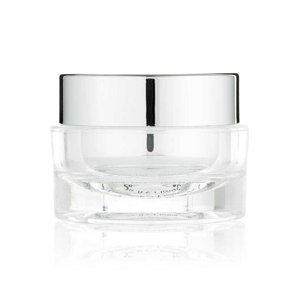 Clear glass beauty jar on a reflective white surface, showing product photography.