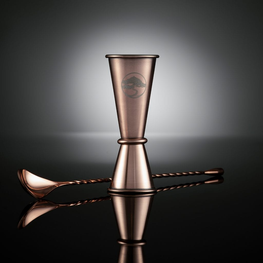 Reflective bronze gin measure with mixing spoon on a gradient black reflective surface and background.