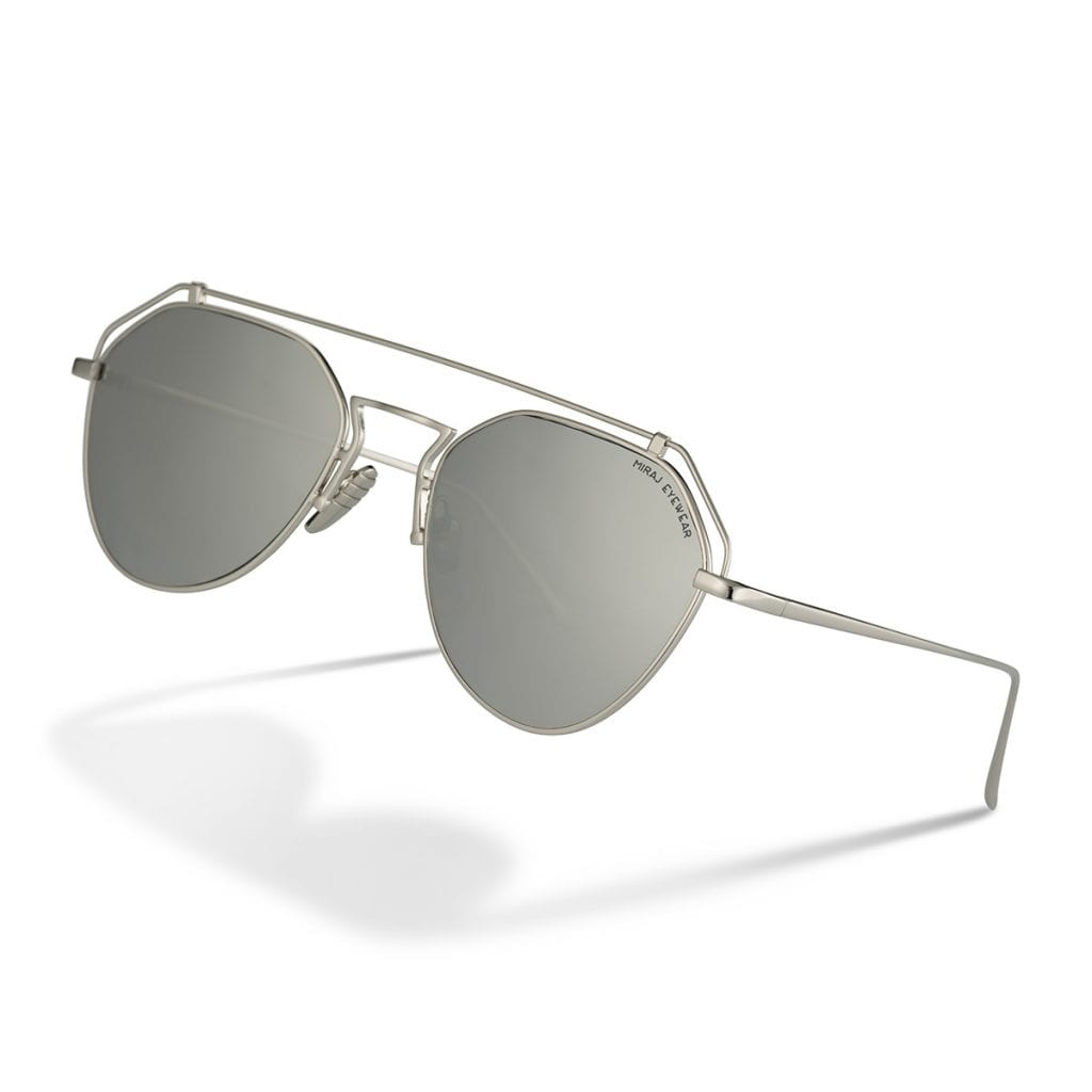 Silver gunmetal sunglasses creatively displayed on a white background with shadows, showing reflective product photography.