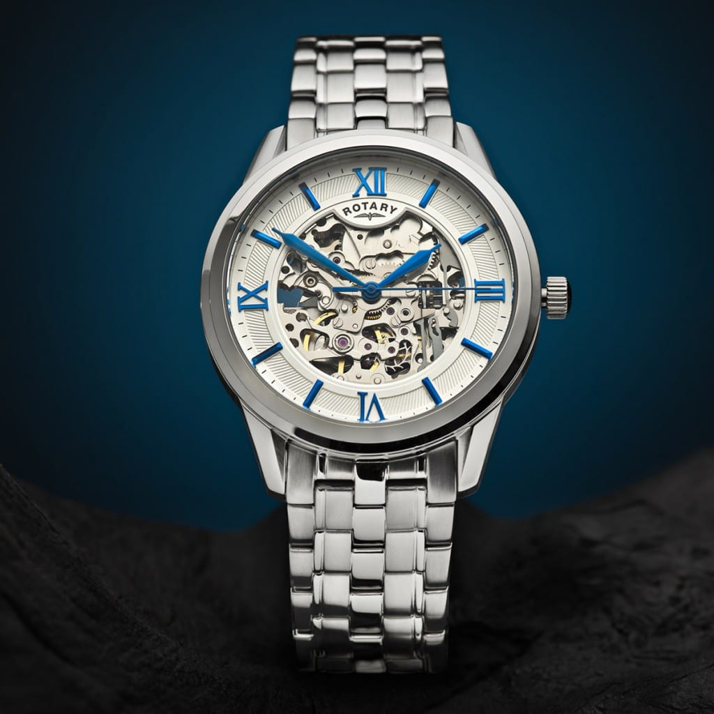 Creative product photography showing a watch shot with a blue gradient background and stone base.